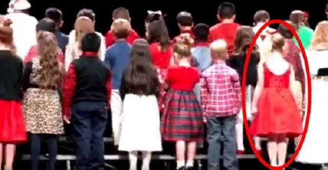 Dzieci ustawiają się na scenie - gdy się odwracają, dziewczynka w czerwonej sukience wywołuje śmiech publiczności
